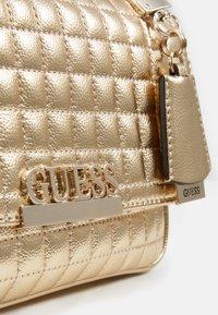 Guess - MATRIX CONVERTIBLE XBODY FLAP - Across body bag - gold - 4
