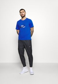 Nike Performance - SHIELD - Tracksuit bottoms - black/reflective silver - 1