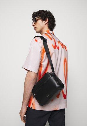 CAMERA BAG EMBOSS UNISEX - Across body bag - black