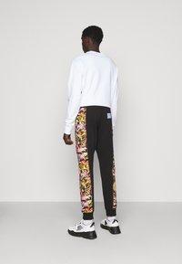 Versace Jeans Couture - HEAVY PRINT VERSAILLES - Tracksuit bottoms - black - 2