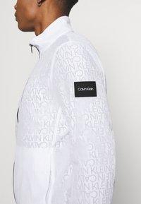Calvin Klein - TRANSPARENT RIPSTOP LOGO BLOUSON - Summer jacket - white - 6