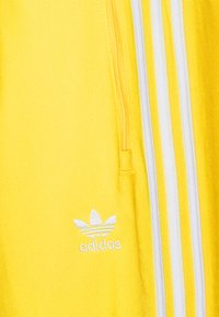 adidas Originals - FIREBIRD UNISEX - Tracksuit bottoms - yellow - 2