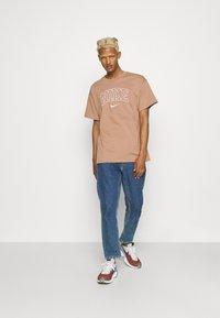 Nike Sportswear - RETRO TEE - Print T-shirt - desert dust - 1