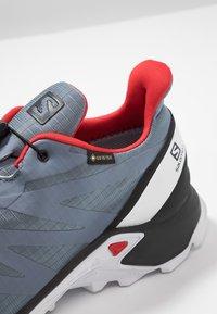 Salomon - SUPERCROSS GTX - Trail running shoes - flint stone/black/high risk red - 5