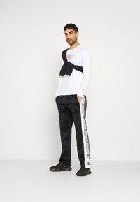 Champion - STRAIGHT HEM PANTS - Tracksuit bottoms - black - 1