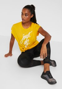 Nike Performance - DRY SIDE TIE  - T-shirt z nadrukiem - university gold/white - 1