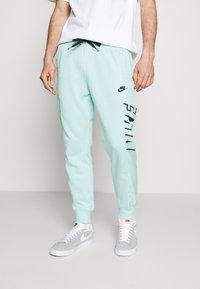 Nike Sportswear - Tracksuit bottoms - light dew/black - 0