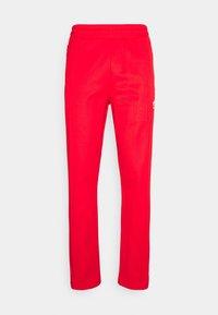 adidas Originals - BECKENBAUER UNISEX - Tracksuit bottoms - red - 4