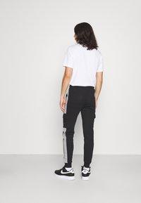 CLOSURE London - TECH UTILITY - Tracksuit bottoms - black - 2