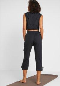 Nike Performance - YOGA PANT CROP - 3/4 sports trousers - black/white - 2