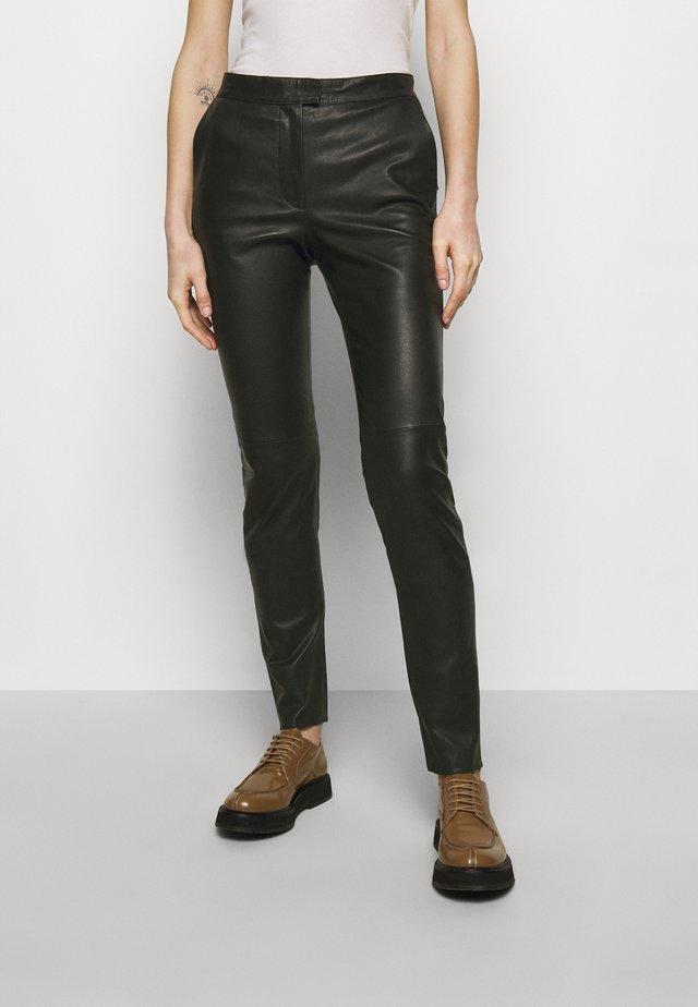 TAIKA - Leather trousers - black
