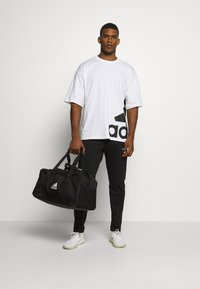 adidas Performance - ESSENTIALS SPORTS REGULAR PANTS - Tracksuit bottoms - black - 1