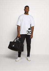 adidas Performance - ESSENTIALS SPORTS REGULAR PANTS - Teplákové kalhoty - black - 1