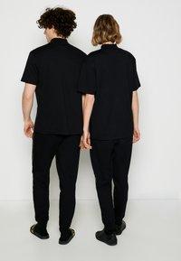 HUGO - DAKAYO METALLIC UNISEX - Print T-shirt - black/gold - 2