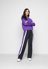 Fila Tall - BECCA TRACK PANTS OVERLENGTH - Verryttelyhousut - black/ultra violet/bright white - 1