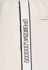 Pegador - WIDE TRACKPANTS UNISEX - Pantalon de survêtement - whisper white - 7