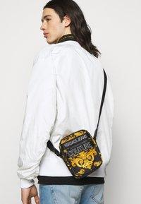 Versace Jeans Couture - UNISEX - Across body bag - black/gold - 1