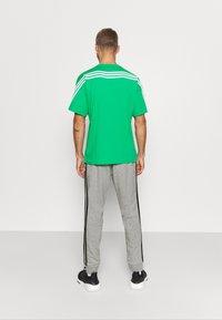 adidas Performance - Tracksuit bottoms - medium grey heather/black - 2