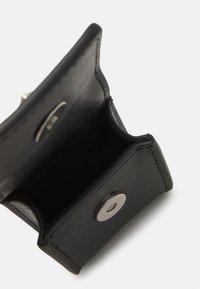 Guess - CERTOSA EARPHONE HOLDER UNISEX - Autres accessoires - black - 1