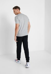 Champion - CUFF PANTS - Tracksuit bottoms - black - 2