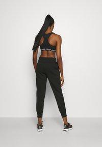 Puma - Pantalon de survêtement - black - 2
