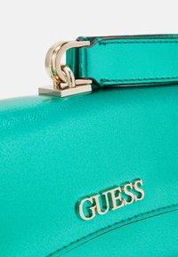 Guess - DEVIN CROSSBODY WRISTLET - Handbag - green - 5