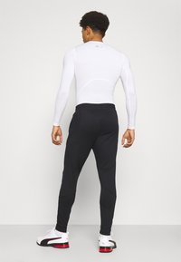 Under Armour - STORM PANTS - Tracksuit bottoms - black - 2