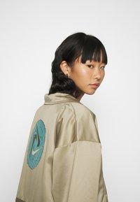 Nike Sportswear - W NSW ICN CLSH LNG JKT SATIN - Veste légère - mystic stone - 4