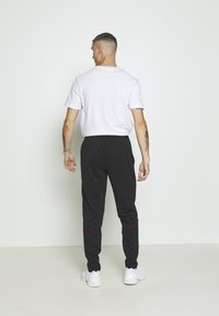 Jordan - JUMPMAN AIR SUIT PANT - Träningsbyxor - black/gym red - 2