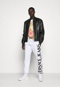 Versace Jeans Couture - BIG LOGO JOGGERS - Trainingsbroek - white - 1