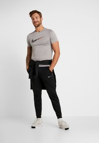 Nike Performance - THRMA TAPER - Tracksuit bottoms - black/mtlc hematite