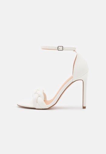 Sandaalit nilkkaremmillä