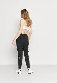 Puma - RUN TAPERED PANT - Pantalones deportivos - black - 2
