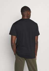 Puma - TRAIN GRAPHIC SHORT SLEEVE TEE - Print T-shirt - black/white - 2