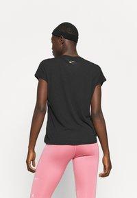 Nike Performance - DRY TIE - Print T-shirt - black/metallic gold - 2