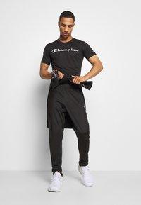 Champion - LEGACY TAPE CUFF PANTS - Tracksuit bottoms - black - 1