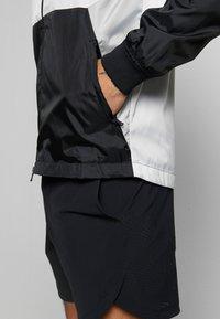 Under Armour - FIELD HOUSE JACKET - Waterproof jacket - white/black - 5
