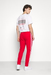 adidas Originals - UNISEX - Tracksuit bottoms - scarle/white - 2