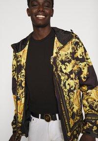 Versace Jeans Couture - T-shirt z nadrukiem - black / gold - 4