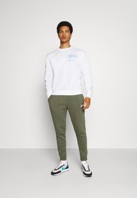 Nike Sportswear - CLUB - Tracksuit bottoms - twilight marsh/white