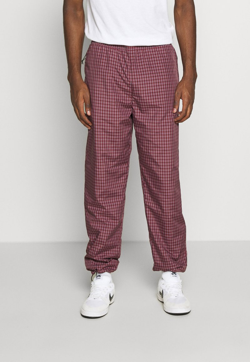 Carhartt WIP - ALISTAIR PANT - Tracksuit bottoms - black/etna red