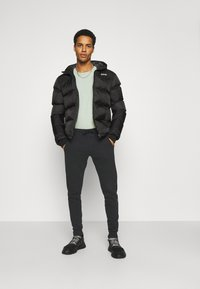 Calvin Klein Jeans - MONOGRAM - Tracksuit bottoms - black - 1