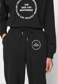Topshop - JOGGER WITH GRAPHIC - Tracksuit bottoms - black - 4
