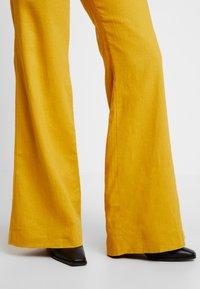 UNIQUE 21 - WIDE LEG TROUSERS - Trousers - mustard - 6