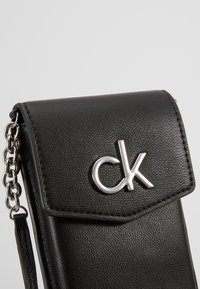 Calvin Klein - RE LOCK PHONE POUCH - Taška spříčným popruhem - black - 2