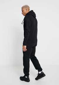 Nike Sportswear - CLUB CUFFED PANT - Tracksuit bottoms - black/white - 2