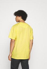 Karl Kani - SMALL SIGNATURE WASHED TEE UNISEX - T-shirt imprimé - light yellow - 2