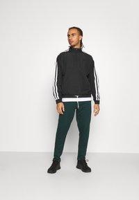 4F - Men's sweatpants - Tracksuit bottoms - dark green - 1
