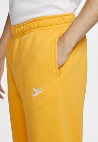 Nike Sportswear - CLUB - Tracksuit bottoms - university gold/white - 4