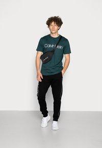 Calvin Klein - LOGO PRINT - Spodnie treningowe - perfect black - 1